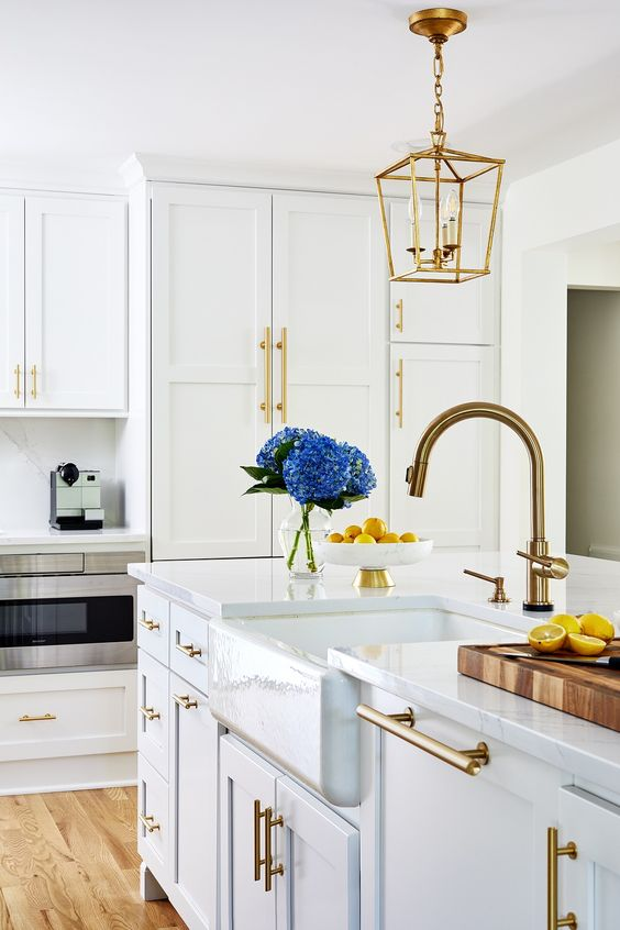 a modern white kitchen with a farmhouse feel, gold fxitures and handles, gold pendant lamps on chains is very chic and stylish