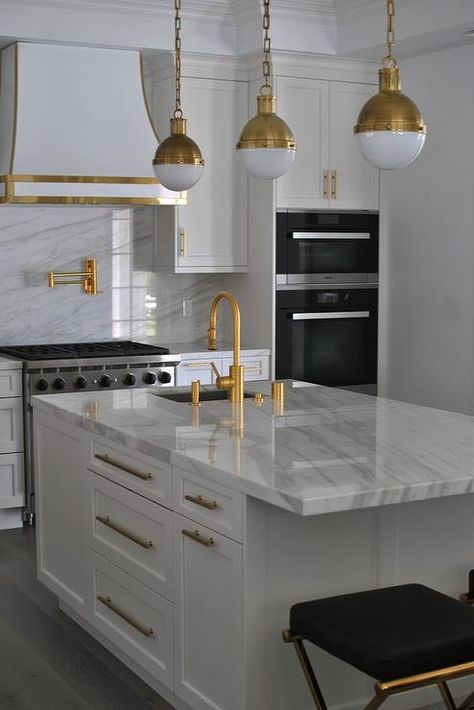 a modern white kitchen with white stone countertops and a backsplash, gold fixtures and a hood lined with gold, gold pendant lamps