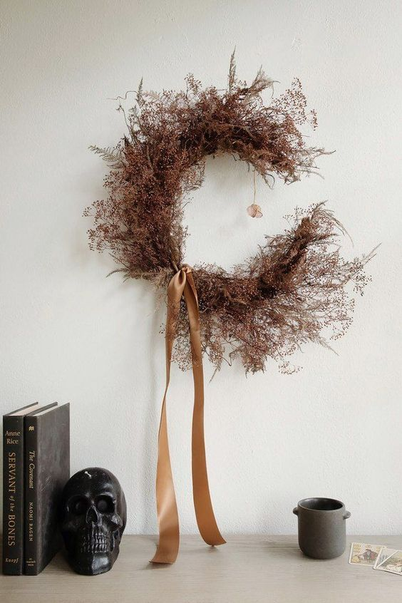 a moody rust-colored branch crescent moon wreath with rust silk ribbons is an out of the box and fresh idea for Halloween