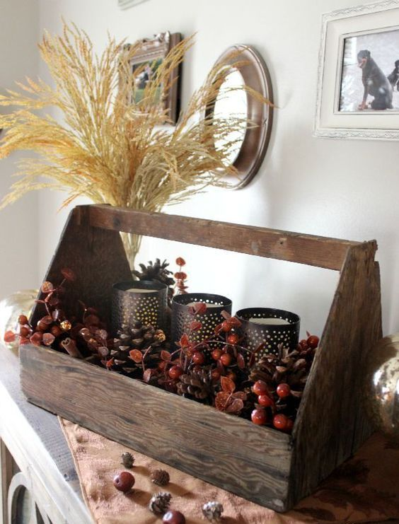 a natural fall centerpiece of a toolbox with berries, cinnamon bark, candleholders and a wheat arrangement