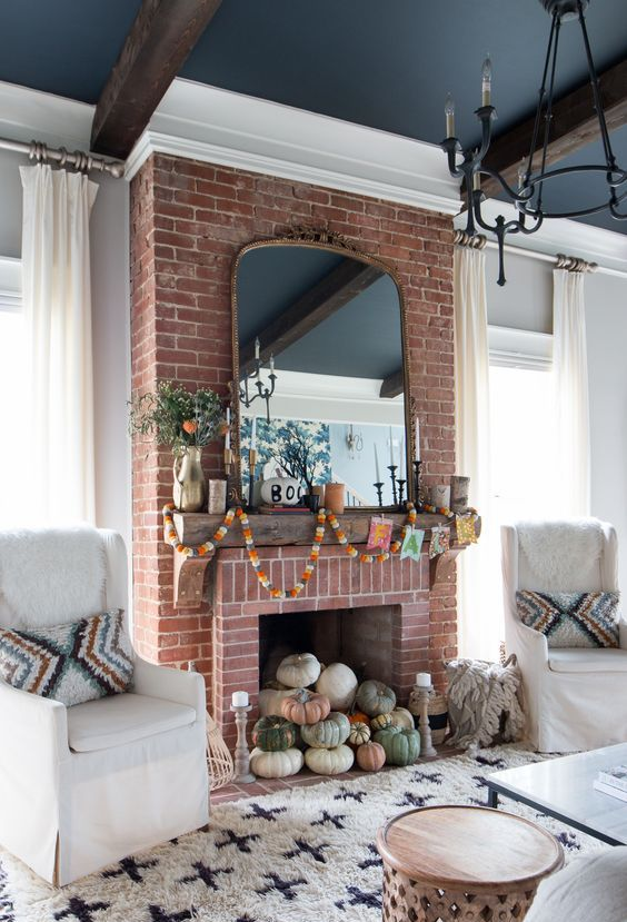 a natural pumpkin stack in the fireplace decorated with fall-colored garlanfs and greenery