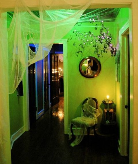 a neon green Halloween space styled with spiderwebs and ghosts,s lights and vintage furniture is pure chic