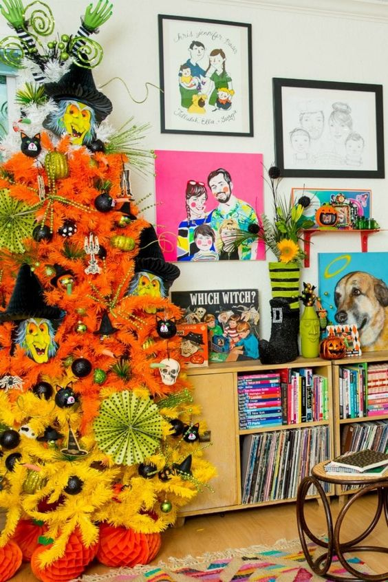 a neon orange and yellow Halloween tree decorated with black, green ornaments, monster masks and skulls is fun