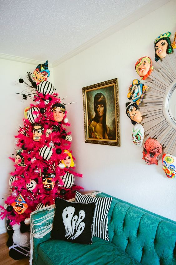 a neon pink Halloween tree decorated with monster masks and black and white oversized ornaments is adorable