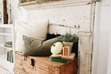 a neutral and relaxed fall fireplace with pillows and greenery, white pumpkins and cocnrete pots for a vintage feel
