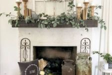 a neutral fall fireplace wwith shabby chic churns, white pumpkins and wheat, wooden candle holders and much greenery