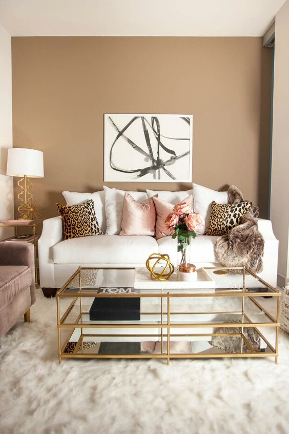 a neutral to muted living room with a white sofa, printed pillows, a printed artwork, a table lamp and a dusty pink sofa