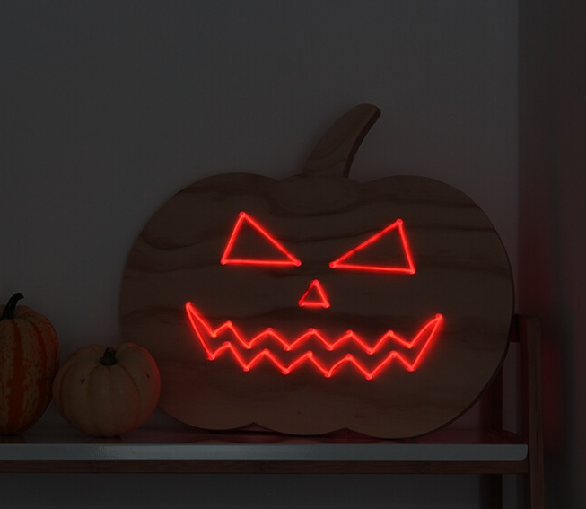 a plywood pumpkin decorated with red neon is a fantastic alternative to carving it