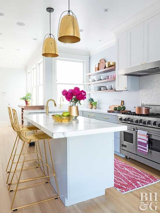 a pretty coastal kitchen done with pale blue cabinets,, gold fixtures, gold pendant lamps and tall stools, a pink rug and pink blooms