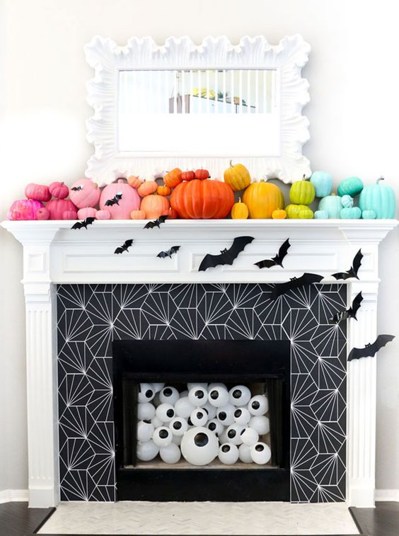 a rainbow pumpkin mantel with bats, eyeballs in the fireplace for fun and bold Halloween styling