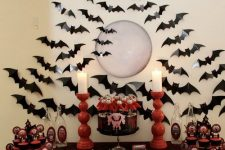 a red and black Halloween dessert table surrounded with black bats, with red candleholders, red and black desserts
