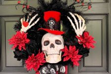 a red and black Halloween wreath of fabric blooms, feathers, branches, skeleton hands and a skull wearing a top hat