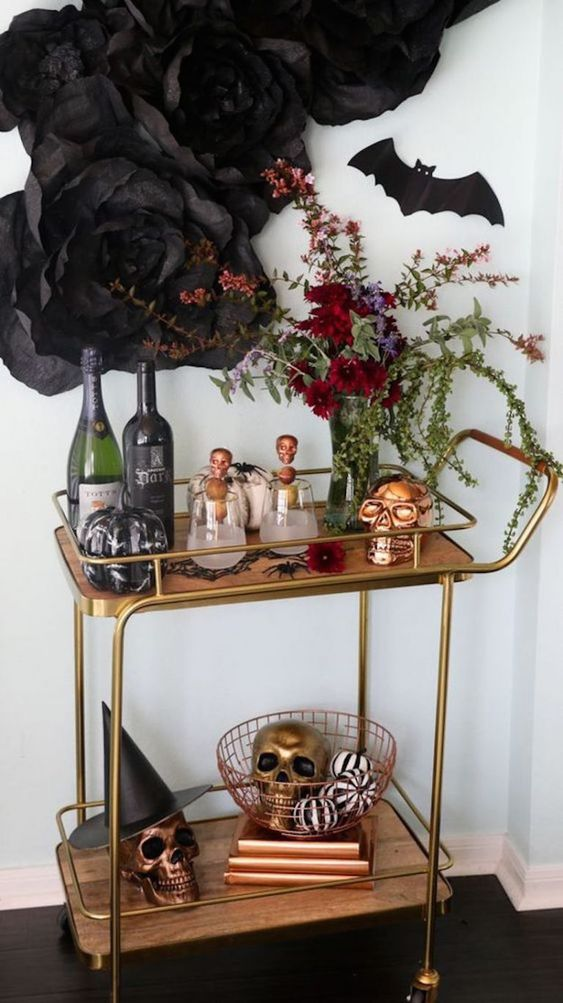 a refined Halloween bar cart with a burgundy and greenery centerpiece, brass and copper skulls, a bat and black paper blooms over it