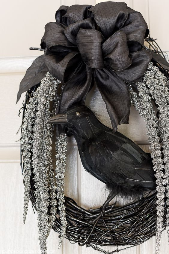 a refined Halloween wreath of black vine, hanging whitewashed blooms, a black black silk bow and a blackbird is classics for Halloween