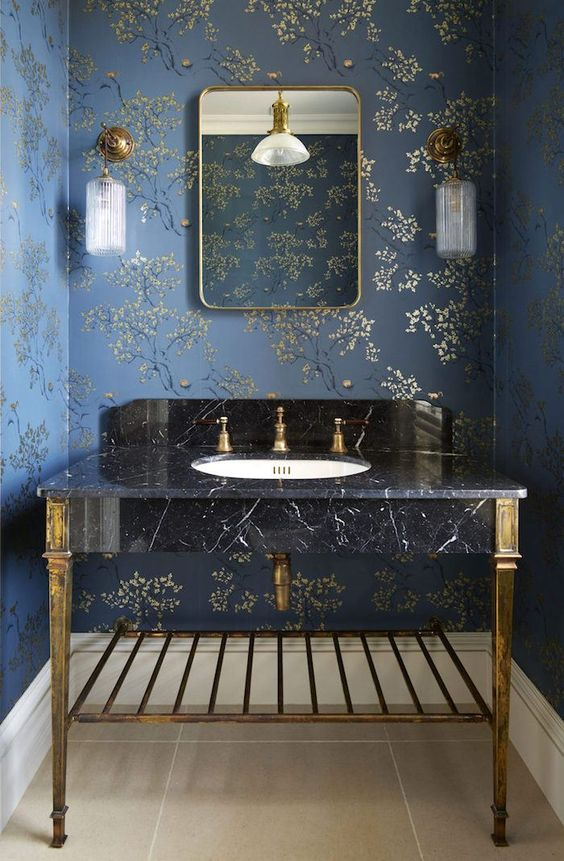 a refined bathroom with navy and gold floral wallpaper, a black marble sink on gold legs and gold fixtures, a mirror in a gold mirror and gold sconces