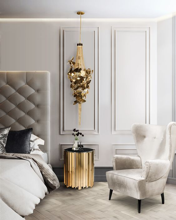 a refined bedroom done in creamy and dove grey, with a bed with an oversized headboard, a wingback chair, a gold nightstand and a gold butterfly pendant