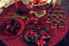 a refined drink station with a black and red spiderweb tablecloth, black and red plates, an exquisite punch bowl and red candles