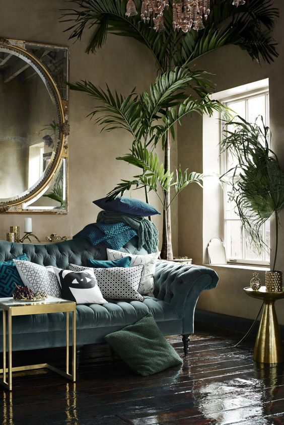 a refined living room with a moody feel, a pale blue sofa, green and blue textiles, potted plants, gilded coffee tables, a crystal chandelier and a large mirror in a gilded frame