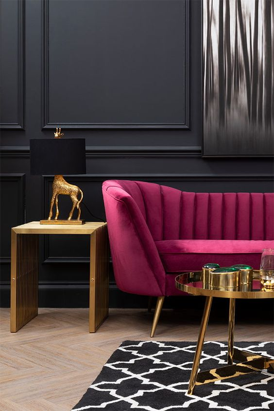 a refined living room with black paneled walls, a fuchsia loveseat, a gold table and a gold side table, gold and black table lamp