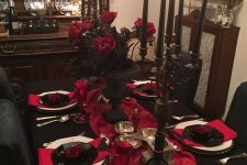 a refined red and black Halloween tablescape with black candelabras and black candles, red roses and red linens