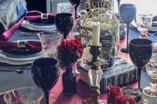 a refined red, black and gold Halloween tablescape with red blooms in black vases, black goblets, a cage, some books and red linens