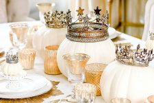 a refined white and gold Halloween tablescape with gold placemats, candleholders and crowns on pumpkins is amazing