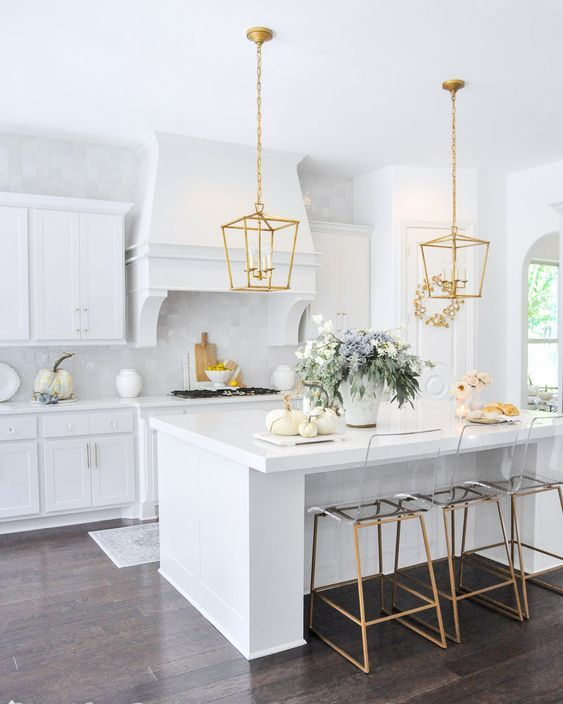 a refined white kitchen with a gold pendant lamp and matching stools is a beautiful and lovely space to enjoy