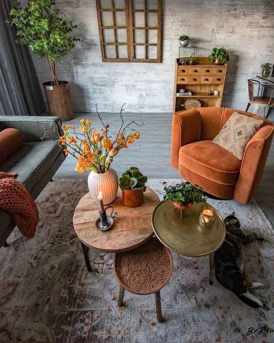 a rust colored chair, blanket, bright coffee tables and bold orange blooms add fall coloring to the living room