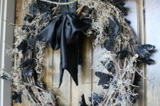 a shabby Halloween wreath of vine, hay, black leaves and a blackbird on top plus a black silk bow is amazing