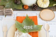 a simple Thanksgiving table with fall leaves, berries, pumpkins, pillar candles and touches of orange