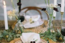 a simple Thanksgiving table with woven placemats, tall candles, dark blooms and lots of greenery