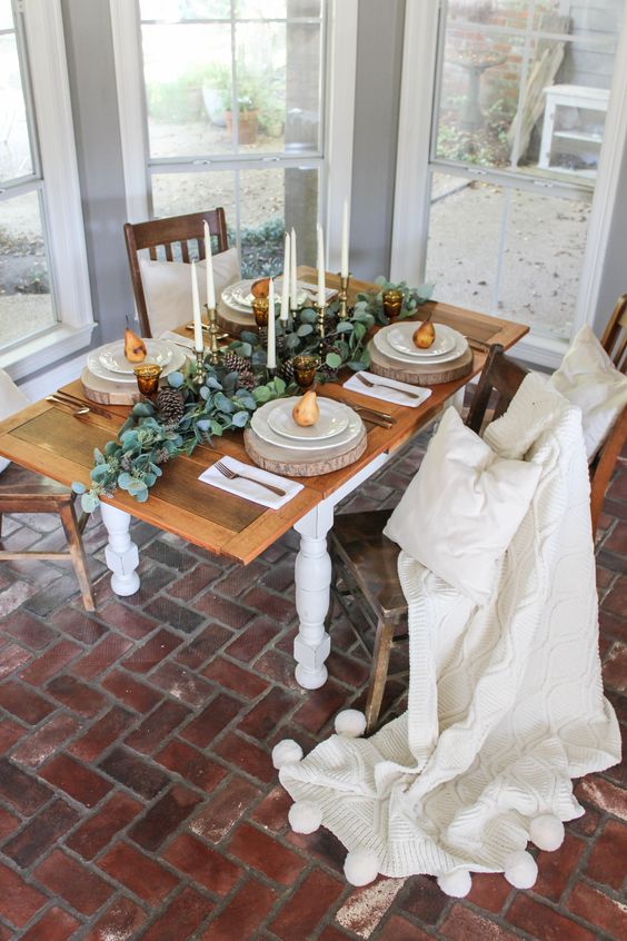 a simple Thanksgiving tablescape with tall candles, a greenery and pinecone runner, wood slices and pears on each place setting
