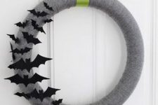 a simple and pretty grey Halloween wreath accented with black paper bats on one side is a cool solution for Halloween