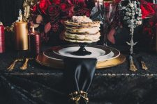 a sophisticated Halloween tablescape with plenty of burgundy and red blooms, burgundy and gold candles, gold chargers and cutlery
