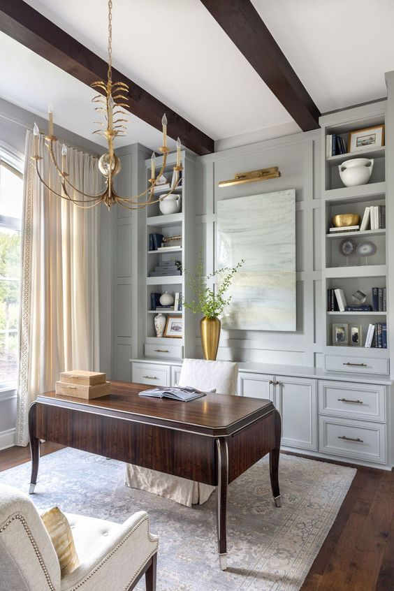 a sophisticated vintage-inspired home office with light grey cabinets, a dark stained desk, delicate gold touches - a chandelier, a lamp, a vase and pillows