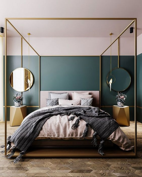a statement glam bedroom with a parquet floor, a gold canopy bed, gold faceted nightstands and mirrors in gold frames