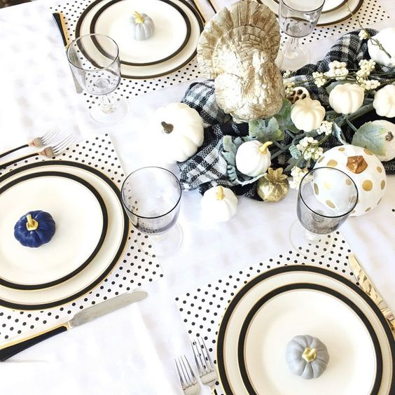 a stylish Thanksgiving tablescape with polka dot placemats, black edge plates, pumpkins, a plaid runner and greenery