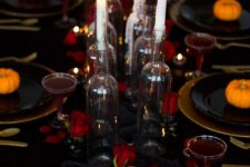 a stylish black, gold and red Halloween tablescape with red roses, candles, skulls, gold chargers and cutlery plus red drinks