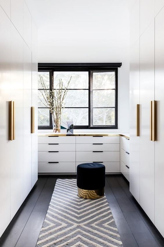 a stylish modern closet with white wardrobes and dressers with gold handles and gold touches here and there, a black pouf with a gold base