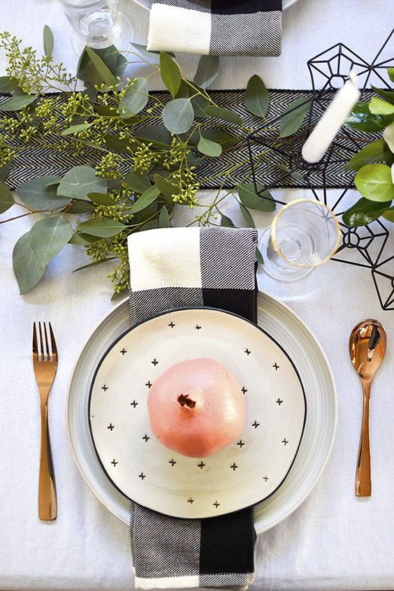 a stylish monochromatic Thanksgiving table with a printed runner, greenery, white candles, printed napkins and plates and gold touches