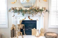 a white and gold Halloween fireplace with greenery, skulls, a skeleton, candles and bats