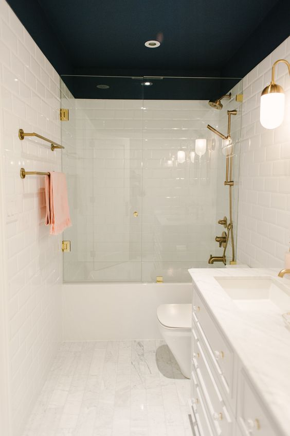 a white bathroom with a black ceiling, gold fixtures and gold sconces is a very chic and contrasting space