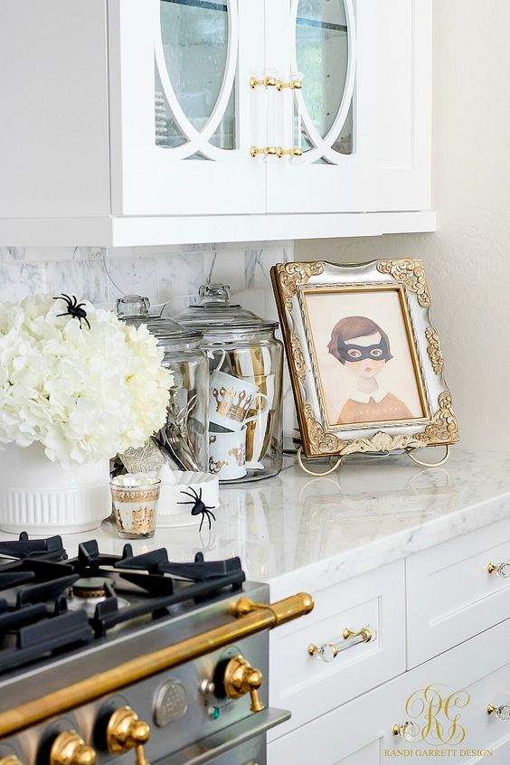 a white floral arrangement with spiders, jars with glam striped and crown mugs and a cool artwork in a refined frame