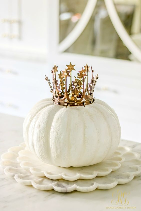 a white pumpkin with a gold crown is an adorable Halloween centerpiece with a strong glam feel