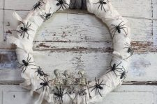 a white wrapped Halloween wreath covered with black spiders, skeletons and a black ribbon is a pretty and simple idea