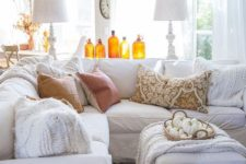 amber colored bottles and a basket with white pumpkins make this white living room more fall-like