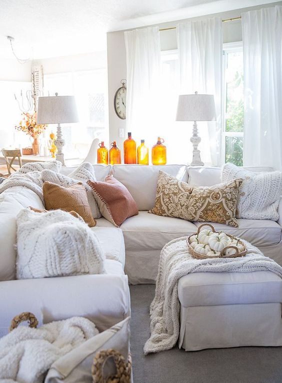 amber colored bottles and a basket with white pumpkins make this white living room more fall like