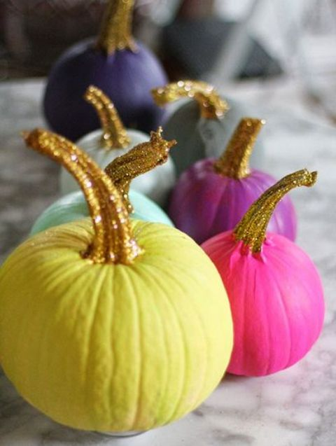 an arrangement of colorful pumpkins with glitter stems for an ultimate glam Halloween party