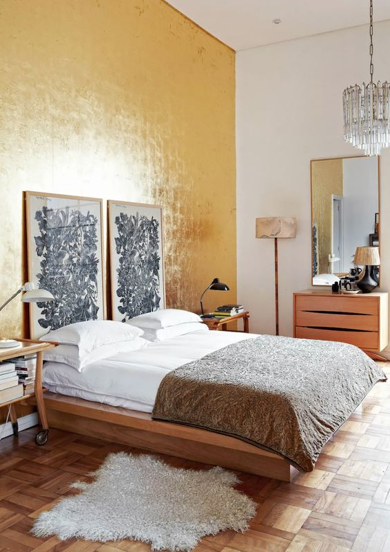 an eclectic bedroom with a shiny gold accent wall, a simple bed with catchy art, a matching dresser and cart nightstands