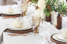 an elegant Thanksgiving table with wooden chargers, candles, amber glasses and apothecary bottles plus white pumpkins